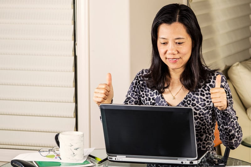 Mature women giving thumbs up on data results while working at home office